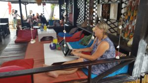 Sarah working in Thailand, sitting in a cafe at The Treehouse on Silent Beach