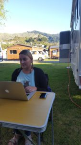 Sarah sat at a camping table working on her laptop