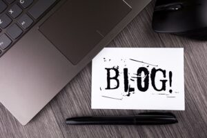 Picture of a laptop with a sign saying blog next to it